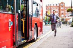捉住公共汽车站的商人赛跑 免版税库存照片