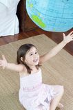 捉住可膨胀的地球的亚洲,混合的族种女孩 免版税图库摄影