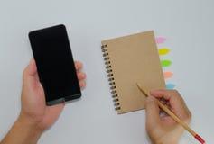 捉住在白色ba的智能手机纸笔记本封面 免版税图库摄影