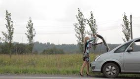 捉住汽车的美丽的妇女在一辆残破的汽车附近 汽车的女性司机问题,紧急情况 股票录像