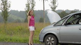 捉住汽车的美丽的妇女在一辆残破的汽车附近 汽车的女性司机问题,紧急情况 影视素材