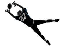 捉住美国橄榄球运动员的人接受剪影 免版税库存图片