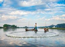 捉住钓鱼鱼的渔夫生长池塘停留三的芦苇标尺 免版税图库摄影
