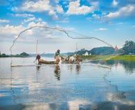 捉住钓鱼鱼的渔夫生长池塘停留三的芦苇标尺 库存图片