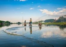 捉住钓鱼鱼的渔夫生长池塘停留三的芦苇标尺 免版税库存图片