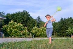 捉住蝴蝶的逗人喜爱的滑稽的小男孩赛跑 库存图片