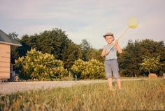 捉住蝴蝶的逗人喜爱的滑稽的小男孩赛跑 免版税库存图片