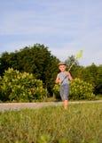 捉住蝴蝶的逗人喜爱的滑稽的小男孩赛跑 库存照片