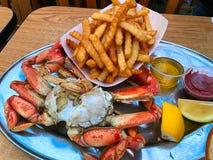 捉蟹在板材用炸薯条、调味汁和柠檬 库存照片