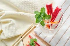 捉蟹棍子用切的红萝卜和萝卜在一块玻璃在织品ba 免版税图库摄影
