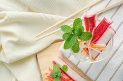 捉蟹棍子用切的红萝卜和萝卜在一块玻璃在织品ba 库存照片