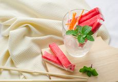 捉蟹棍子用切的红萝卜和萝卜在一块玻璃在织品ba 免版税库存照片