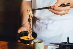 捏与大理石纹理的煮沸的好的做的切片Wagyu在未加工的鸡蛋的手牛肉与筷子和垂度在吃前 免版税库存图片