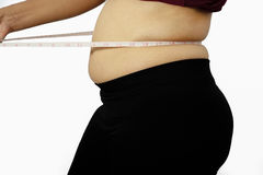 捏她的肥胖肚子的肥胖超重妇女被隔绝在白色背景,肥胖妇女,有肥胖腹部的妇女 库存照片
