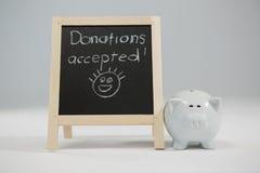 捐赠在与存钱罐的板岩接受了写 库存照片