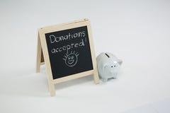 捐赠在与存钱罐的板岩接受了写 图库摄影