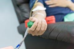 捐赠的献血者与在手中举行一个有弹性的球 库存照片
