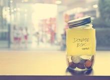 捐赠箱子,在玻璃瓶的硬币,葡萄酒颜色口气 免版税库存照片
