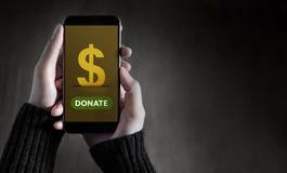 捐赠网上概念,拿着有Applicati的女性巧妙的电话 免版税库存图片