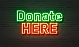 捐赠这里在砖墙背景的霓虹灯广告 免版税库存图片
