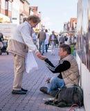 捐钱的夫人给无家可归的人 免版税库存照片