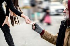 捐钱的妇女的中央部位给坐在城市的无家可归的叫化子人 图库摄影
