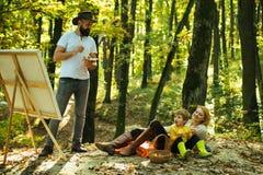 捕获片刻 r 有胡子的人妇女和儿子放松秋天自然 得出从生活 画家艺术家与 免版税库存照片
