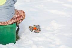 捕鱼冰谎言捕捉冬天zander 为冬天渔的一个工具在手上 一根钓鱼竿在结冰的手上 库存照片