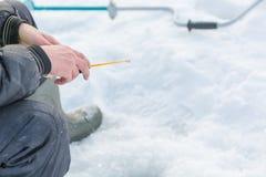 捕鱼冰谎言捕捉冬天zander 为冬天渔的一个工具在手上 一根钓鱼竿在结冰的手上 免版税图库摄影