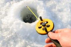 捕鱼冰谎言捕捉冬天zander 拿着标尺的渔夫手降下了入冰孔 特写镜头射击 免版税库存图片