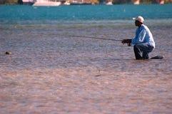 捕鱼指南洪都拉斯下跪 免版税库存照片