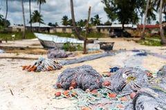 捕鱼网和小船在一个海滩与房子背景的 库存照片