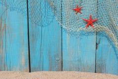 捕鱼网和红色海星反对老木背景 免版税库存照片