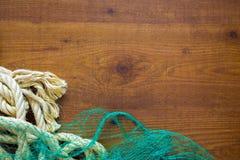 捕鱼网和绳索在木背景 免版税库存图片
