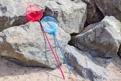 捕鱼网或蝴蝶网在一块石头在海滩附近 免版税库存图片