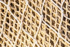 捕鱼网,米黄白色打结了样式,海洋背景 库存照片