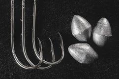捕鱼设备:勾子和在黑暗隔绝的渔坠子 免版税库存照片