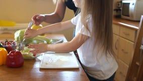 捞出沙拉的逗人喜爱的学龄前女孩在厨房里 妈妈` s帮手 女儿和母亲准备素食沙拉 影视素材