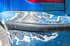 损坏在蓝色有损坏的和被剥皮的油漆的被抓的汽车防撞器在崩溃事故或停车场 免版税库存图片
