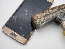 损坏的智能手机显示特写镜头与锤子的 图库摄影