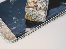 损坏的智能手机显示特写镜头与锤子的 库存照片