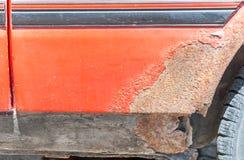 损坏的红色汽车金属身体和被抓的油漆与生锈的被腐蚀的部分和孔在底部准备好车体 库存图片