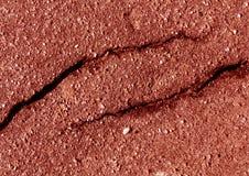损坏的红色被定调子的沥青表面 免版税库存照片