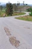 损坏的路和骑自行车的人 库存照片