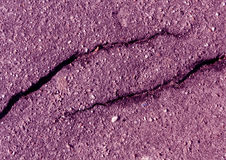 损坏的紫色被定调子的沥青表面 免版税库存照片