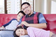 损坏他的长沙发的父亲孩子 免版税库存照片