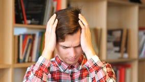 损失和失败翻倒年轻人的,拿着他的头 免版税库存图片
