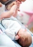 换一个新出生的婴孩的尿布的母亲 免版税库存照片