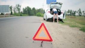 更换一个被刺的轮胎的女孩在汽车 汽车修理在路的 适应 股票视频