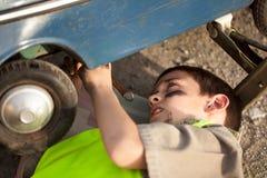 更换在一辆老玩具汽车的年轻男孩一个轮胎 免版税图库摄影